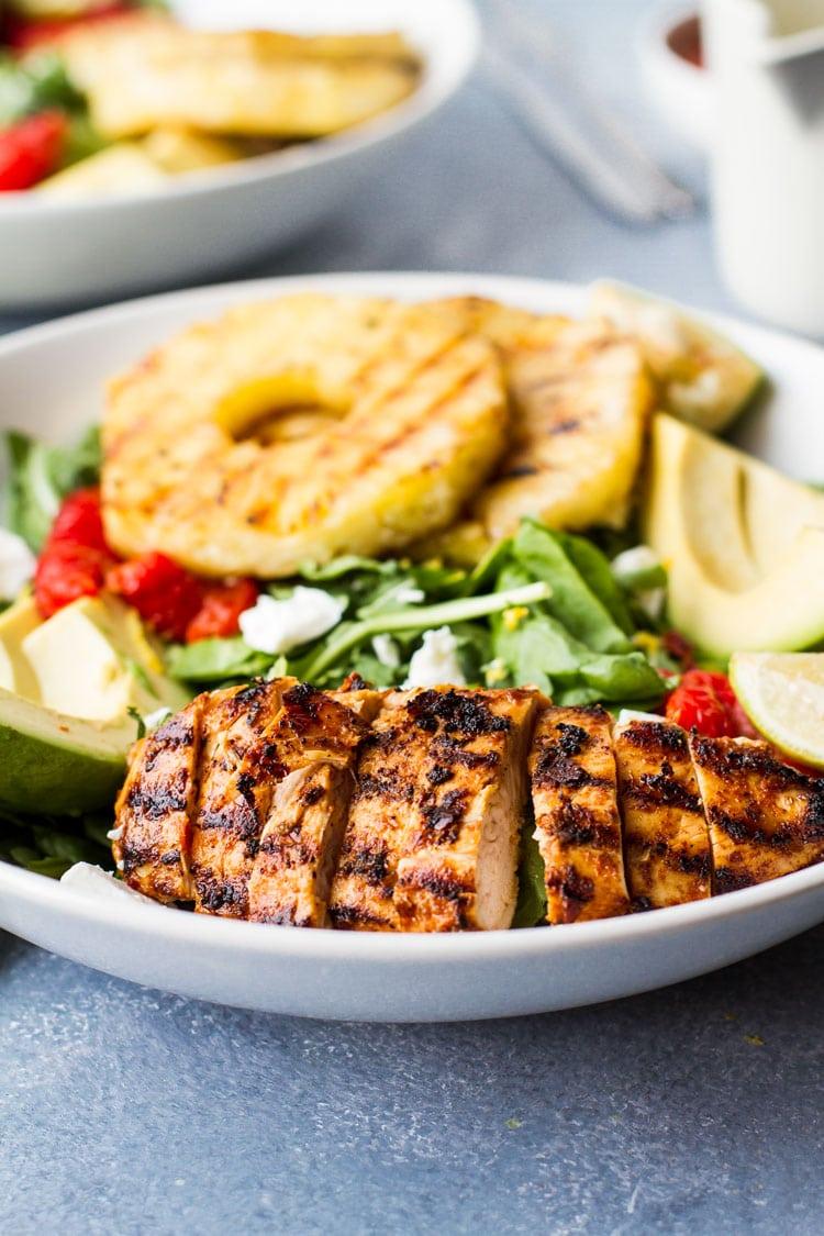 Sliced grilled harissa chicken in a salad bowl.