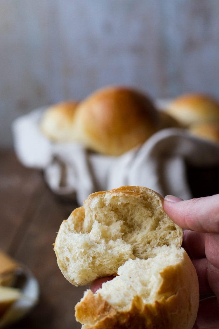 Closeup of an torn open sweet bun. Sweet rolls in a basket in the background.