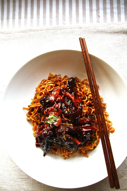 White bowl with fried noodles, beef strips and julienned carrots.