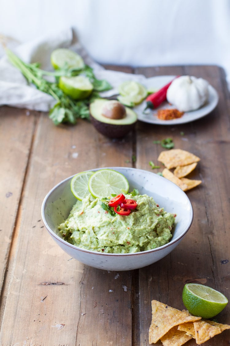 A bowl of guacamole on a wooden board.