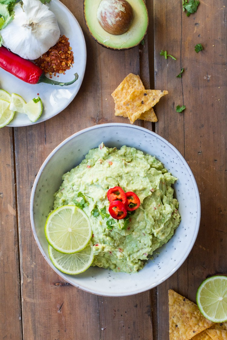 Bowl of guacamole, garnished with lime and chili slices. Flatlay.