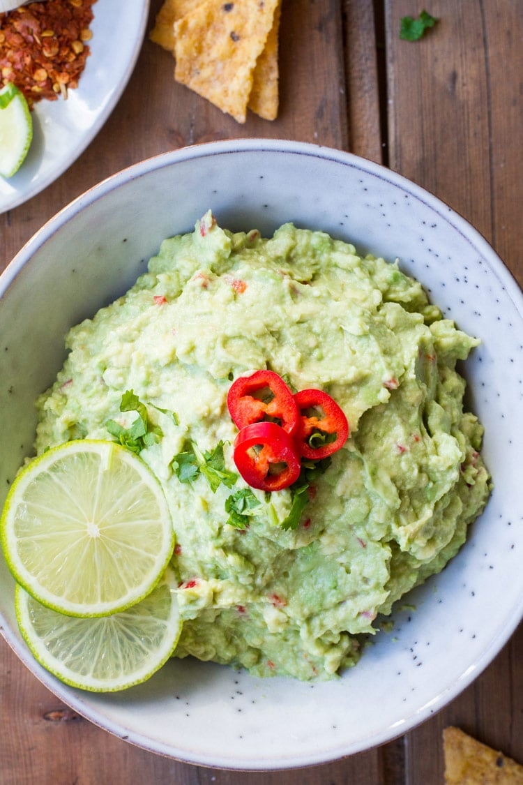 Bowl of guacamole, garnished with lime and chili, closeup.