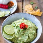 A rustic bowl filled with guacamole and garnished with lime and chili. Square recipe photo.