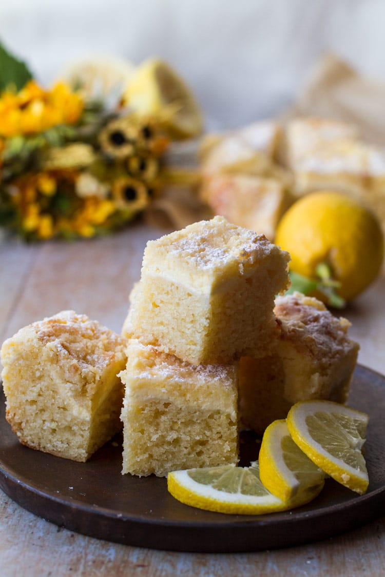 A stack of lemon cake pieces on a wooden plate. Yellow flowers in the back.