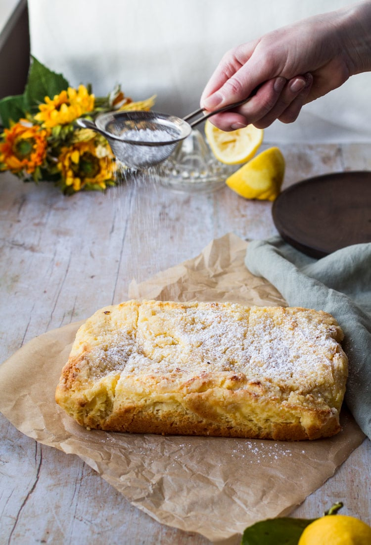 Sprinkling powdered sugar on the cake. Parchment paper as plate. Yellow flowers and lemons in the background.