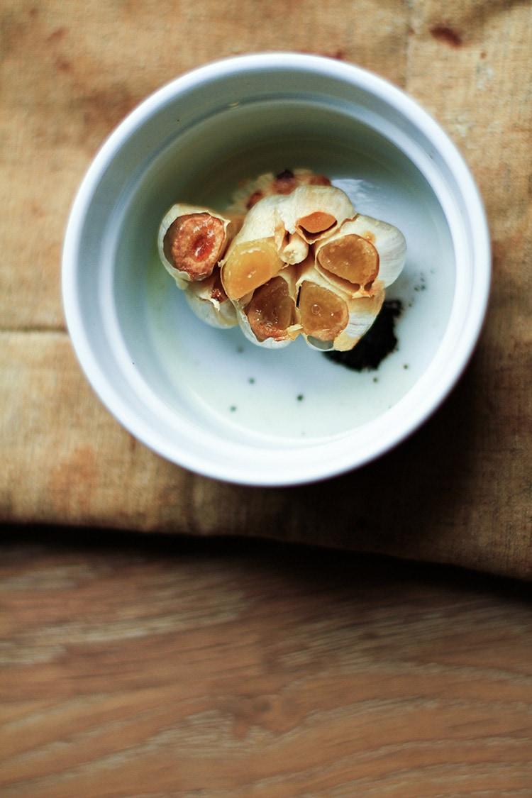 Roasted garlic in a white ramekin.