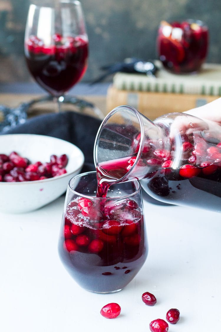 Pouring sangria into a wine glass.