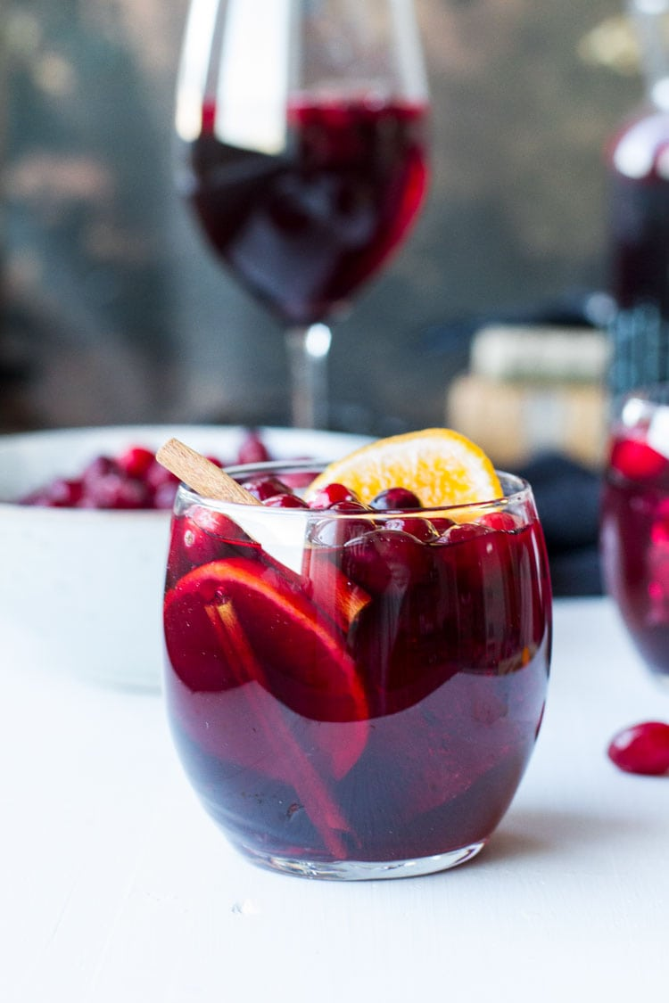 Round glass with cranberry sangria, garnished with fresh cranberries and orange slice.