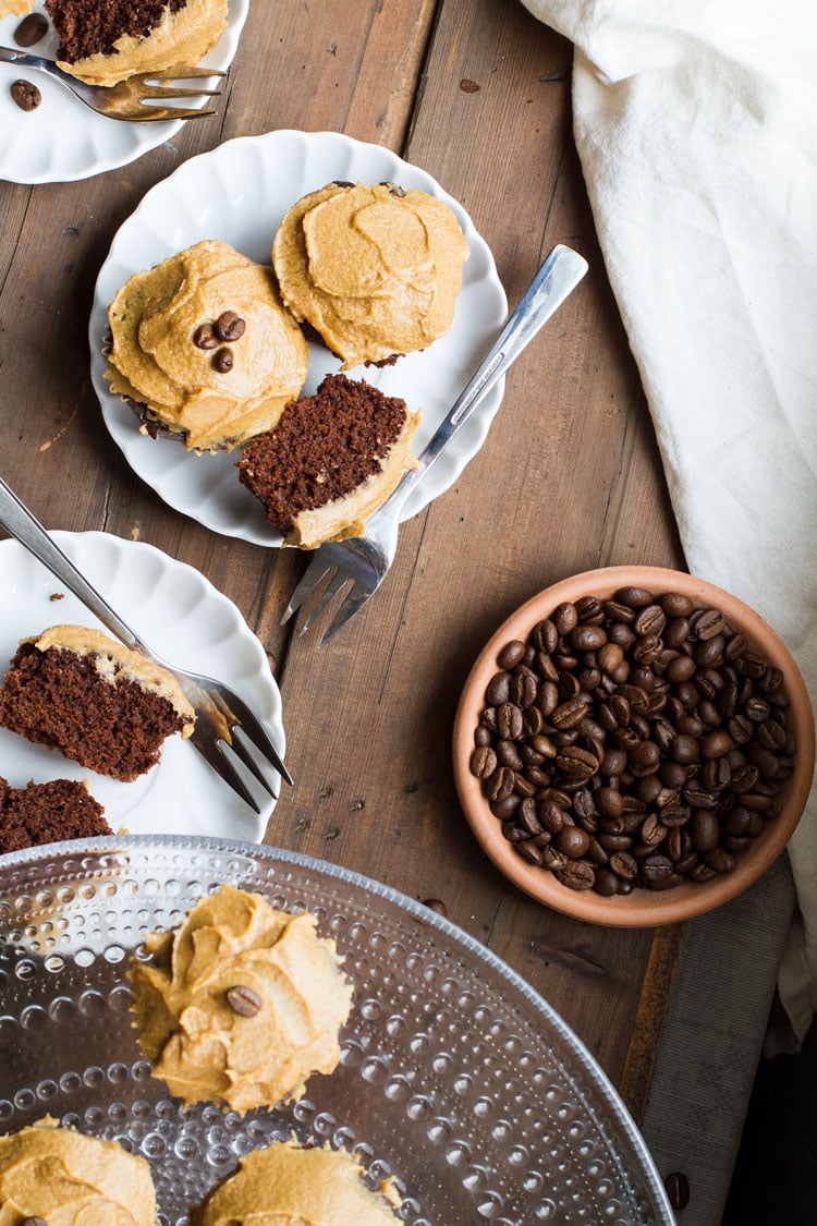 Chocolate coffee cupcakes on a white plate and coffee beans in a small bowl.