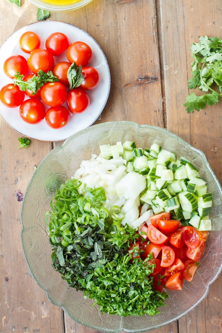 Ingredients to make this tabbouleh recipe, separate in a clear bowl.