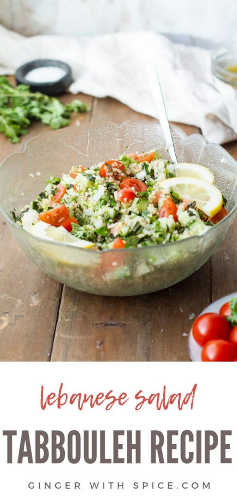 Tabbouleh and lemon wedges in a large glass bowl. Ingredients and towel blurred in the background. Pinterest pin.