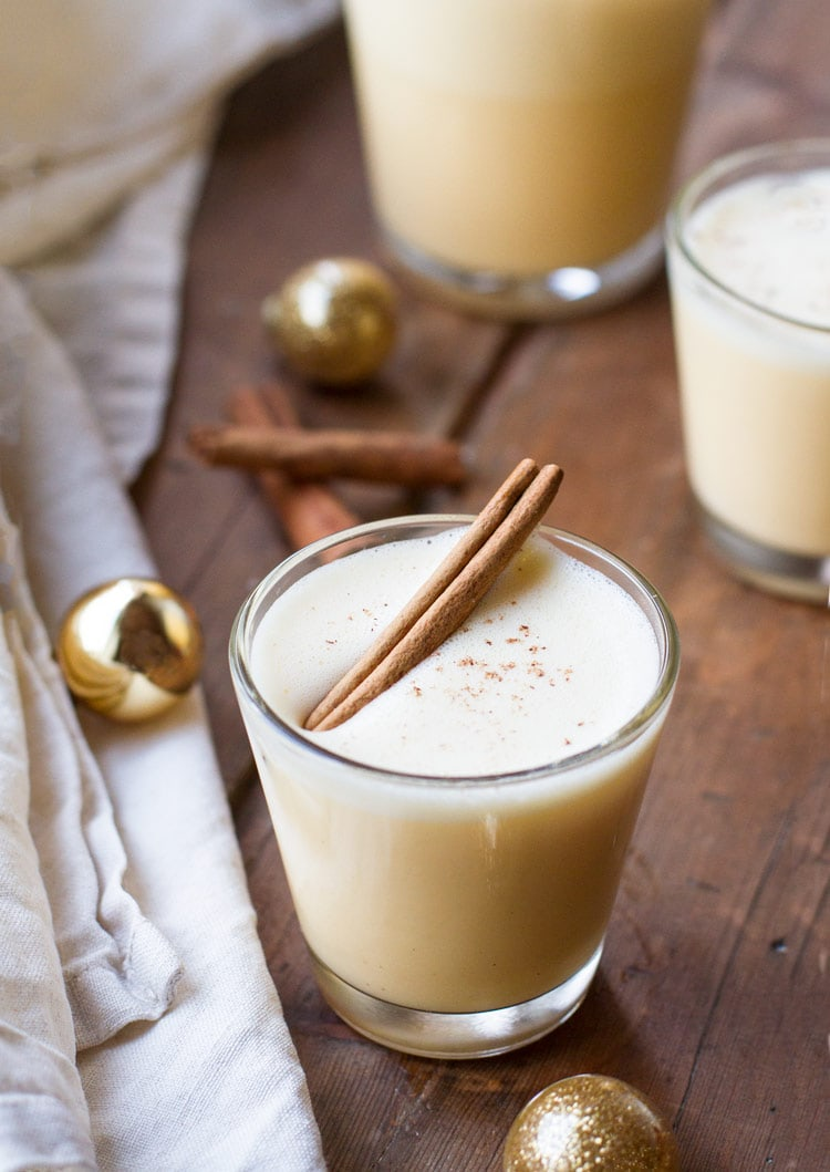 A glass with homemade eggnog with a cinnamon stick floating on the foam.