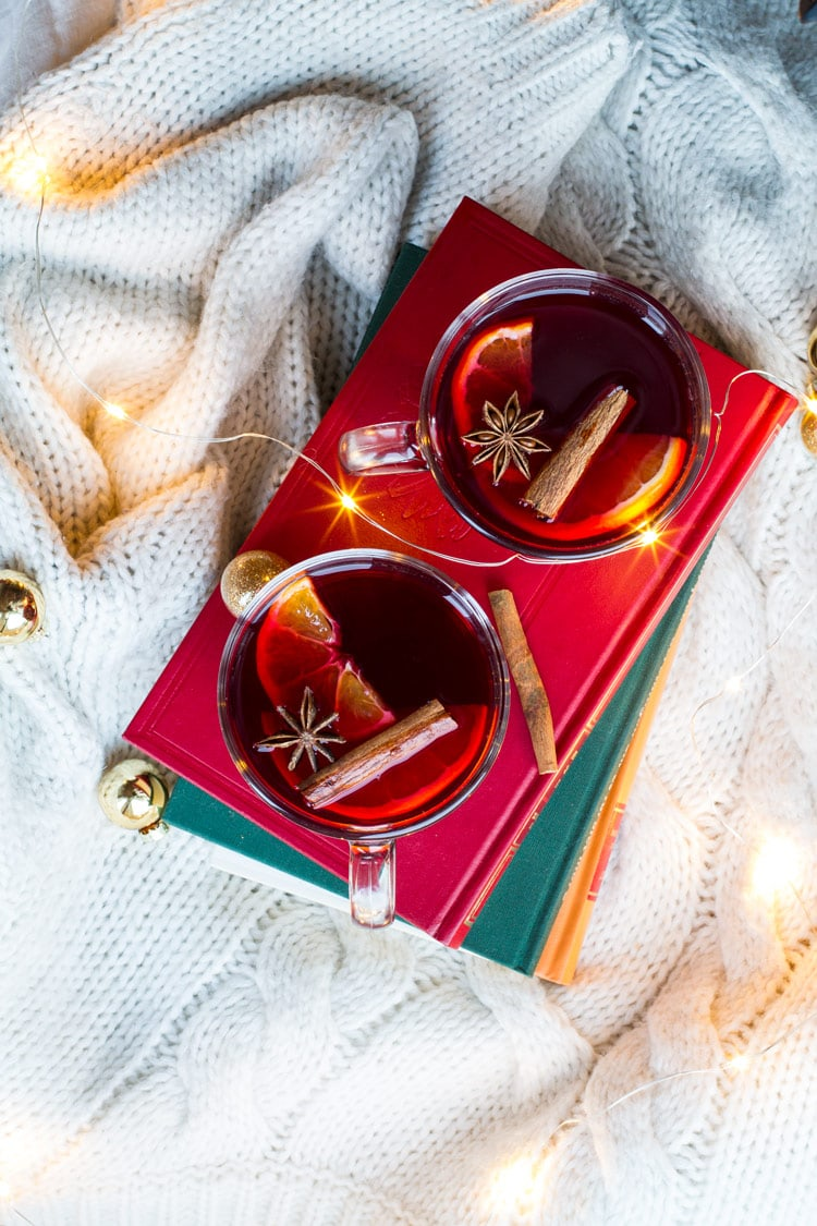 Two glasses with mulled wine, cinnamon sticks, star anise and clementine slices on a red book, white background and flatlay.