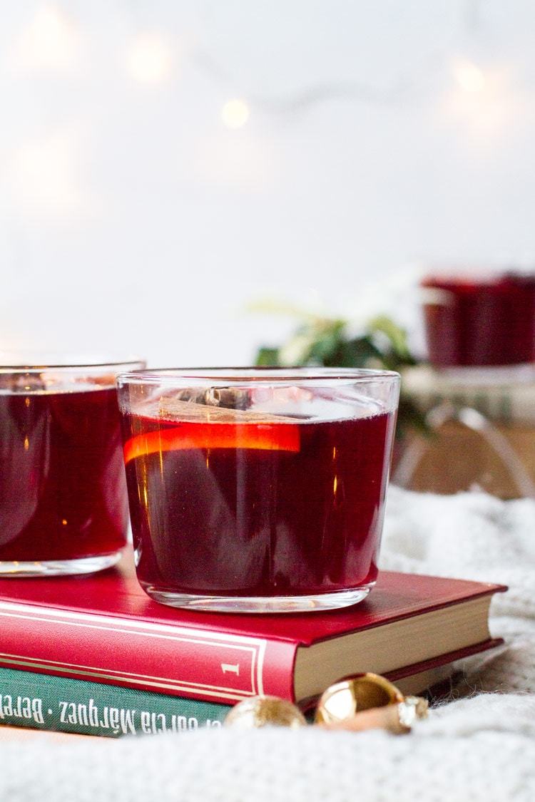 Two glass mugs with mulled wine and orange slices on top of a red book, white background.