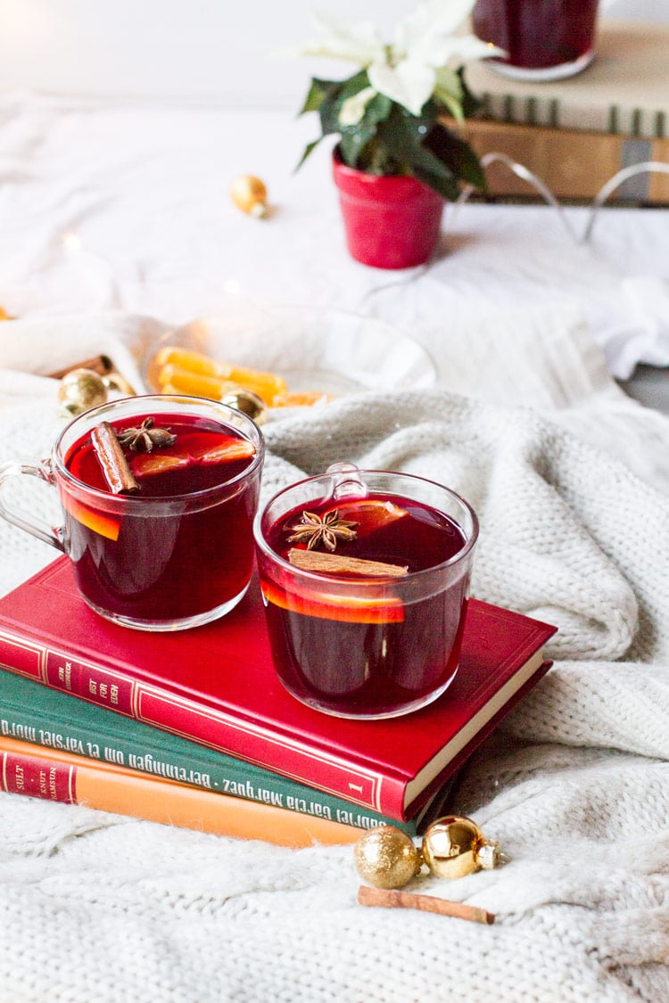 Two glass mugs with mulled wine on top of three old books, white background.