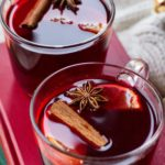 Two mugs with mulled wine garnished with cinnamon stick, star anise and clementine slice.