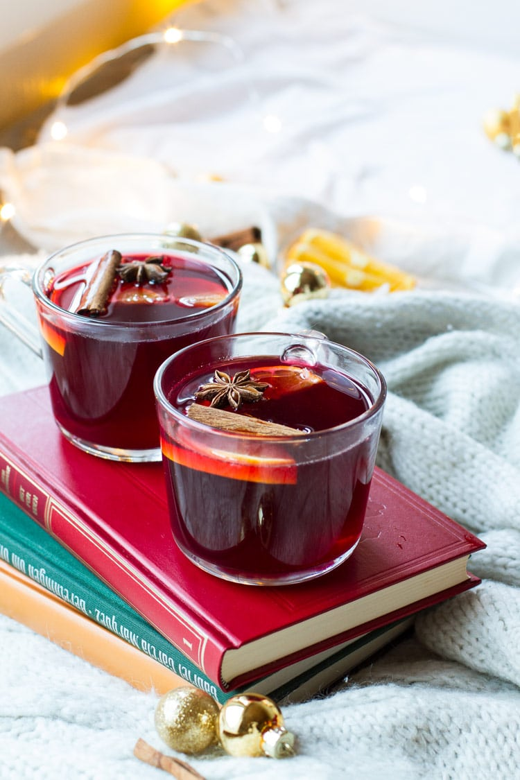 Glass mugs with mulled wine on a red book.