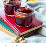 Glass mugs with mulled wine on a red book. Pinterest pin with text.