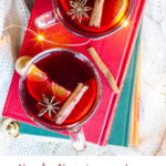 Two glasses with mulled wine, cinnamon sticks, star anise and clementine slices on a red book, white background and flatlay. Pinterest pin.