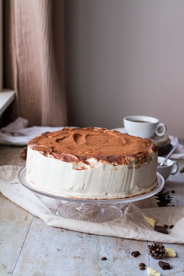 Whole tiramisu cake on a cake stand, nude color background.