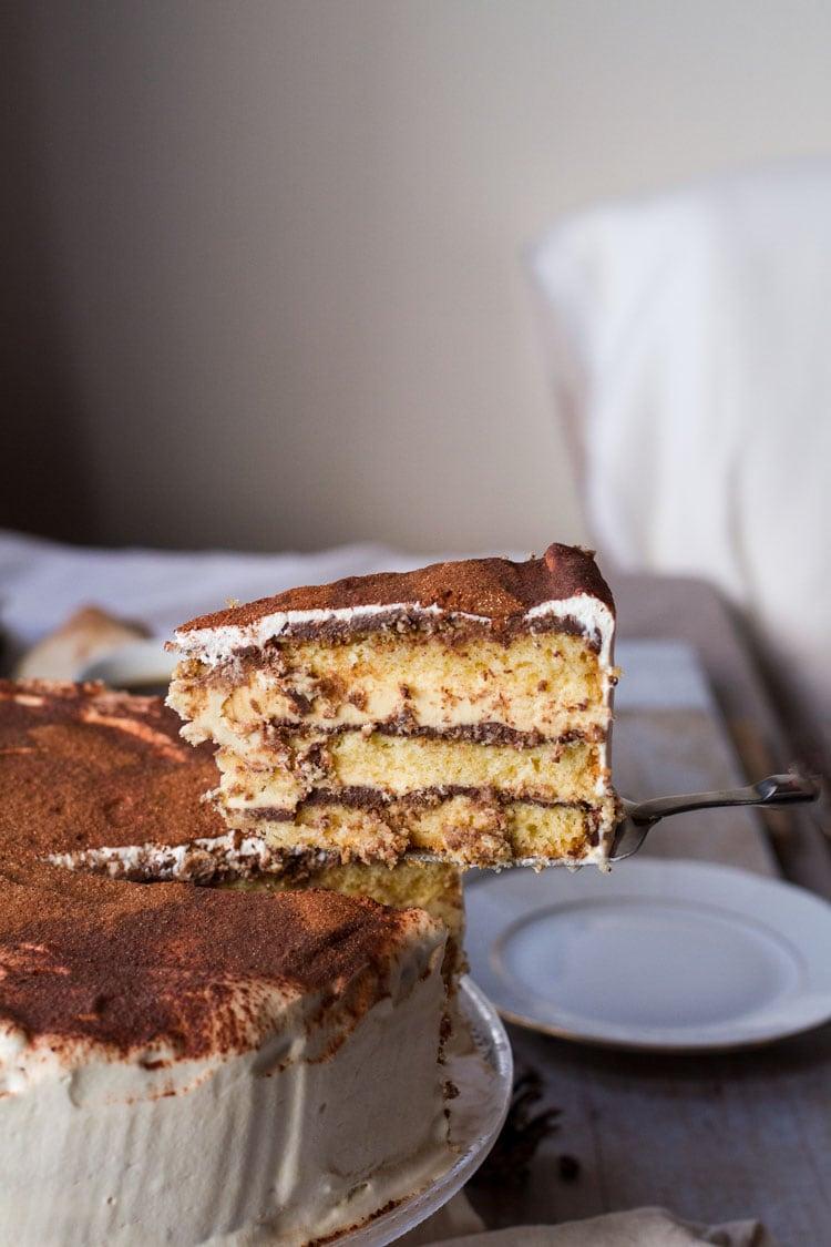 Taking a slice out of the whole tiramisu cake.