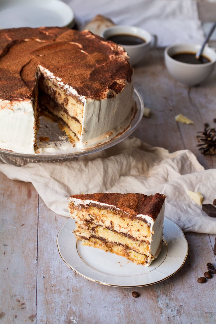 Slice of tiramisu cake on a small white plate, the whole cake in the background.
