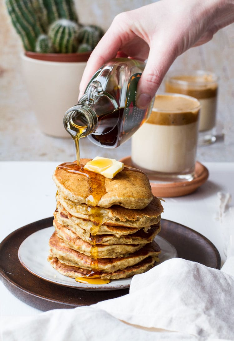 Pouring maple syrup on top of a stack of small pancakes.