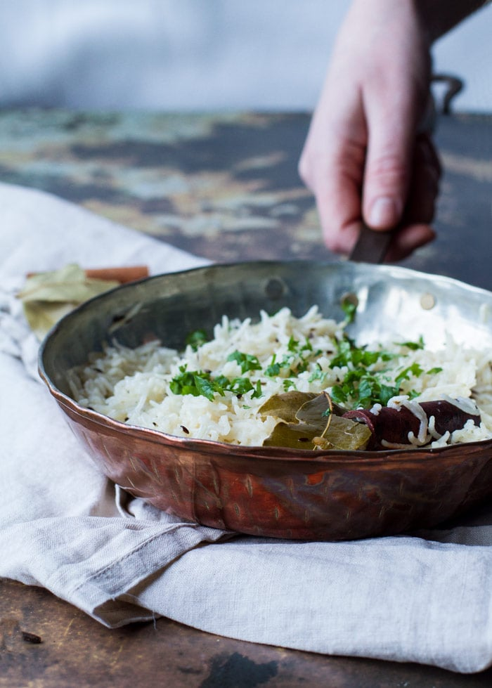 Straight angle of a copper pan with Indian rice with cilantro, cinnamon stick and bay leaf. Hand holding the pan's handle. Rusty background and nude colored cloth.