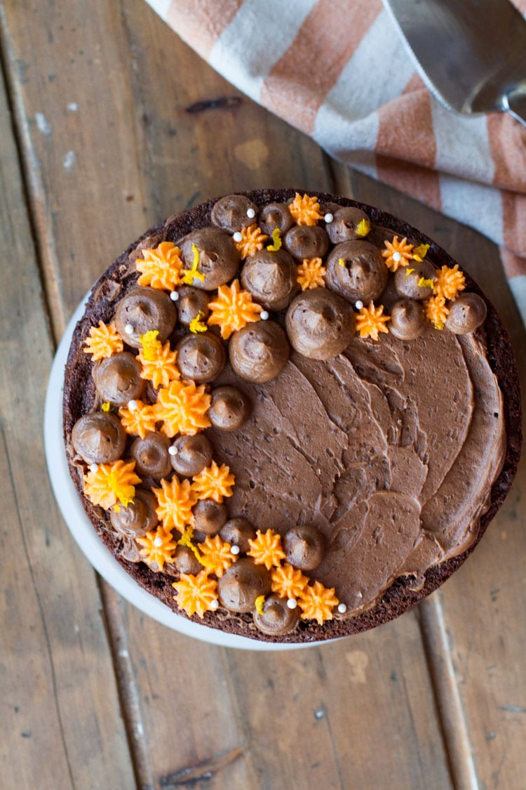 Flatlay of the chocolate cake with orange decorations.