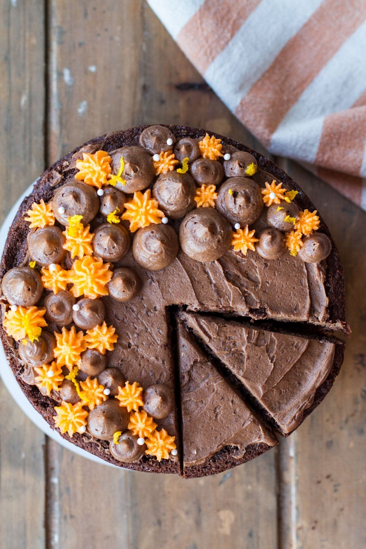Chocolate cake with orange and chocolate droplets on top. Two slices cut. Flatlay.