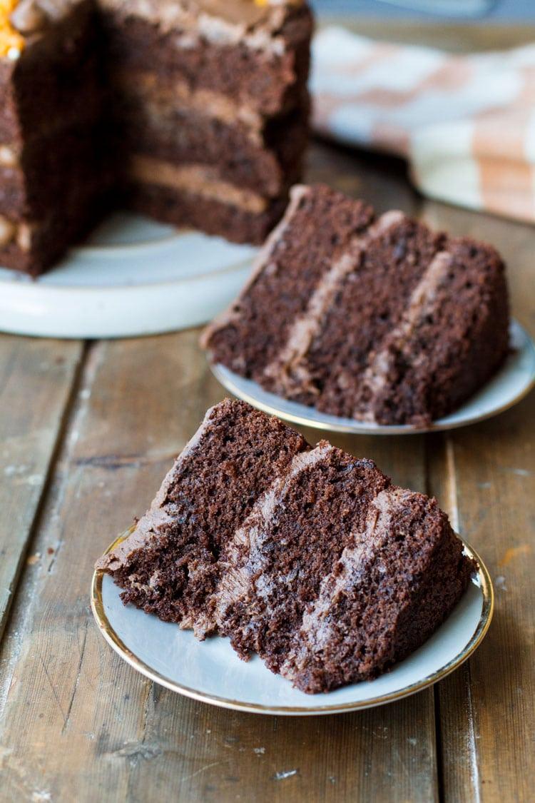 Two plates with orange chocolate cake slices.