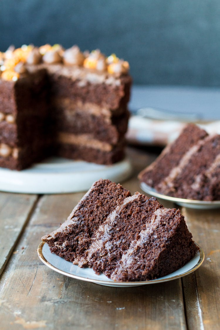 A slice of chocolate cake with chocolate buttercream layered inbetween.