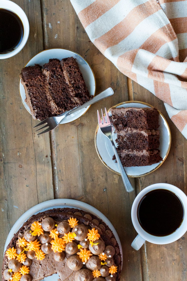 Two plates with slices of orange chocolate cake. The rest of the cake is in the bottom left corner.