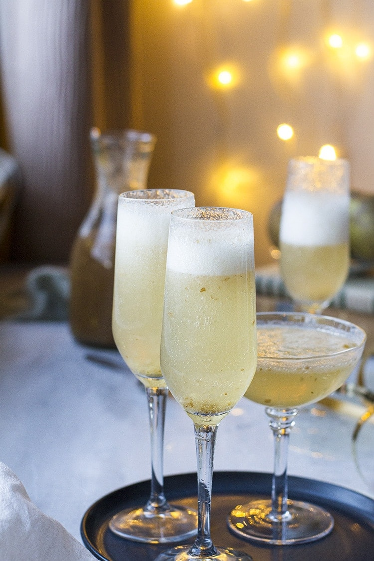 Three champagne glasses with ginger pear bellini.
