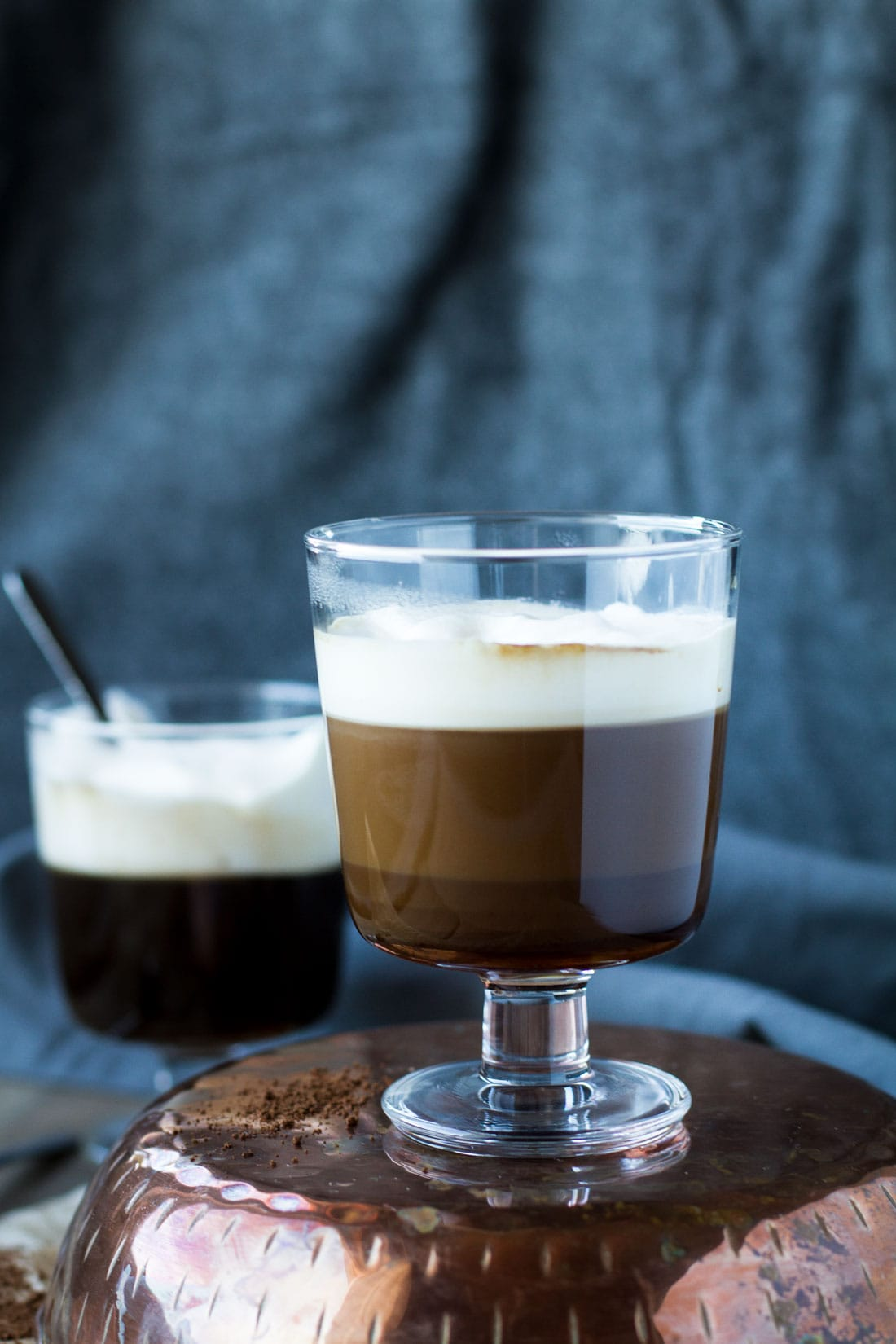 Irish coffee in a clear glass with stem, whipped cream on top.