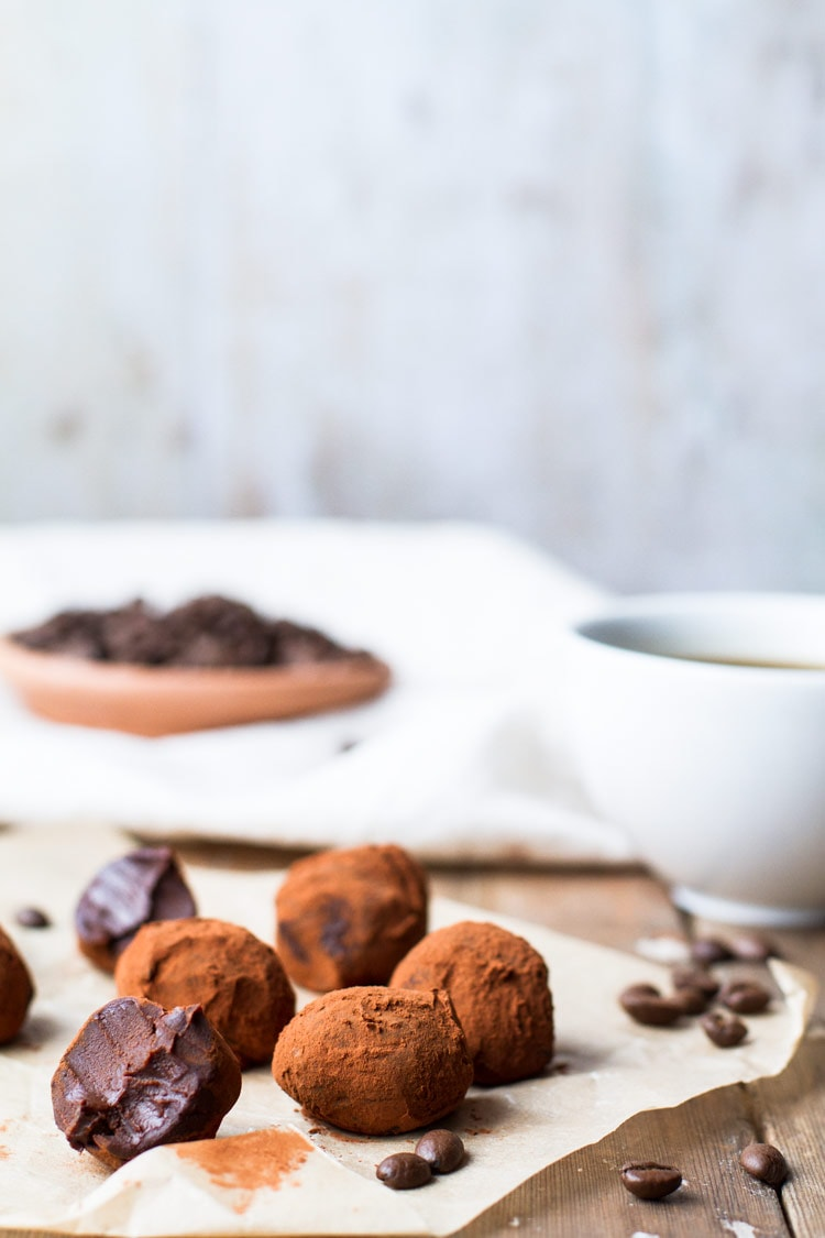 Chocolate Coffee Truffles on brown parchment paper. One is taken a bite of. Covered in cocoa powdered. A plate of coffee beans and a cup of coffee in the background.
