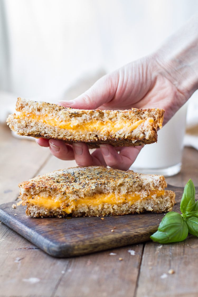 Hand holding one half of a grilled cheese sandwich.