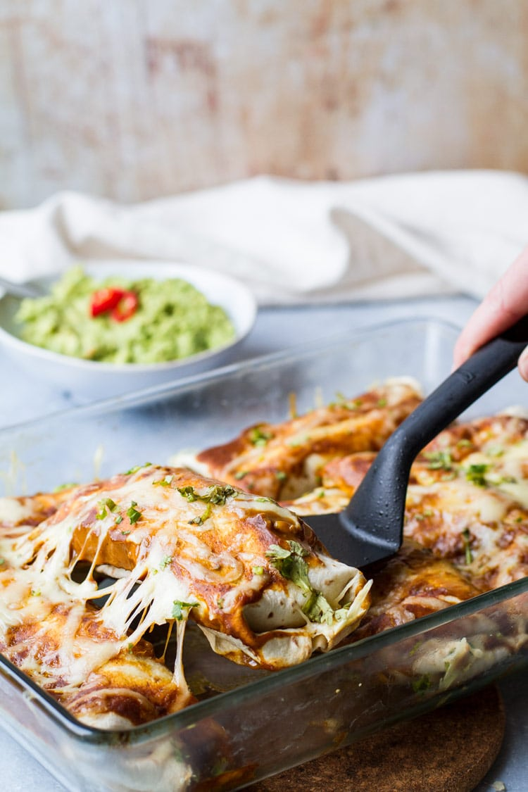 Spatula holding one cheesy enchilada tortilla.