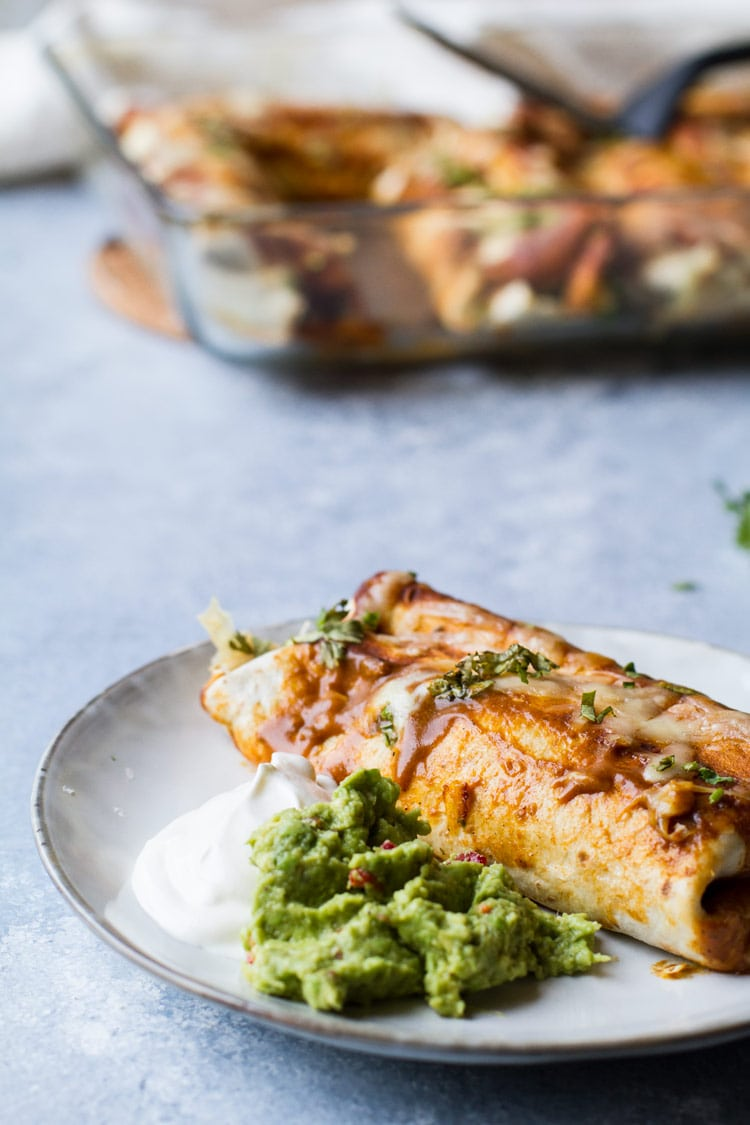 A grey plate with one enchilada, a dollop of guacamole and sour cream.