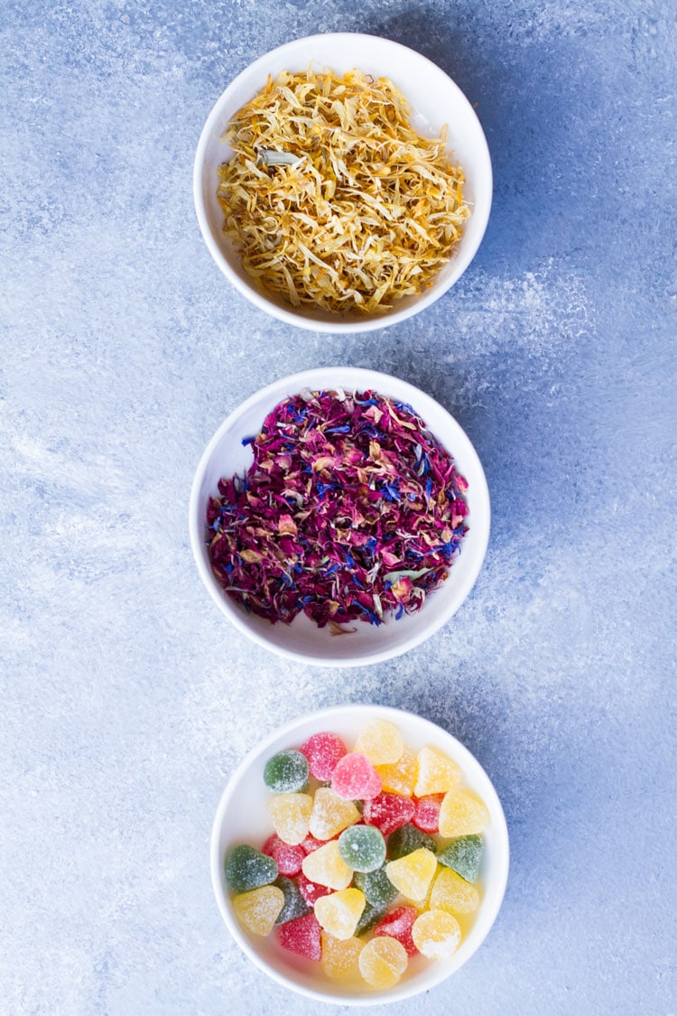 Three bowls with different toppings; yellow flowers, pink flowers and jelly candy.