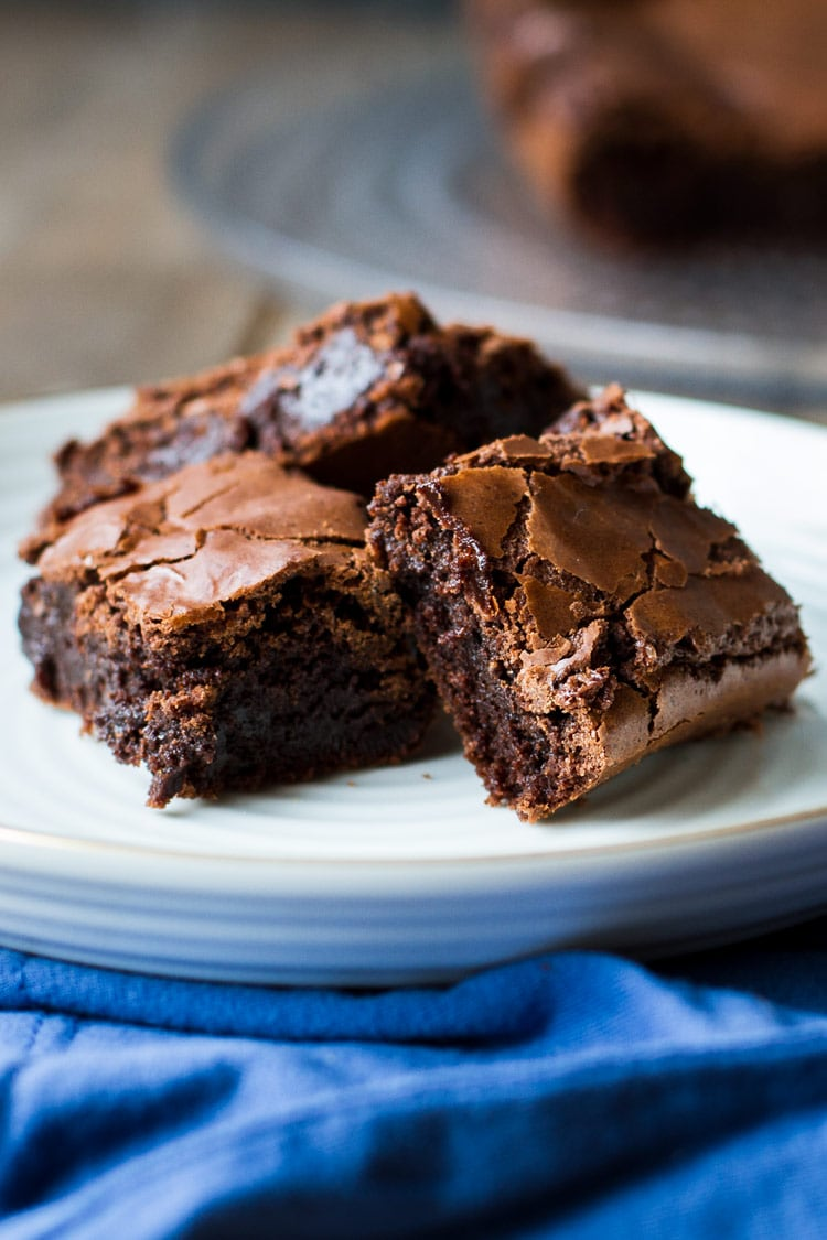 Three brownies stacked on a white plate, blue towel.