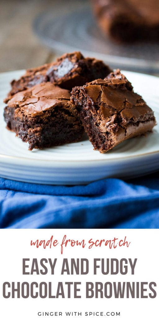 Three brownies stacked on a white plate, blue towel. Pinterest pin.