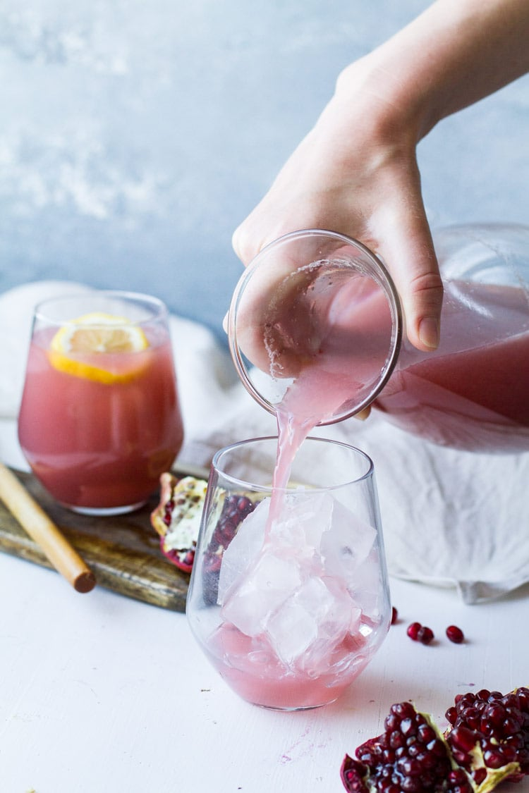 Pouring cucumber pomegranate vodka lemonade into a wine glass.