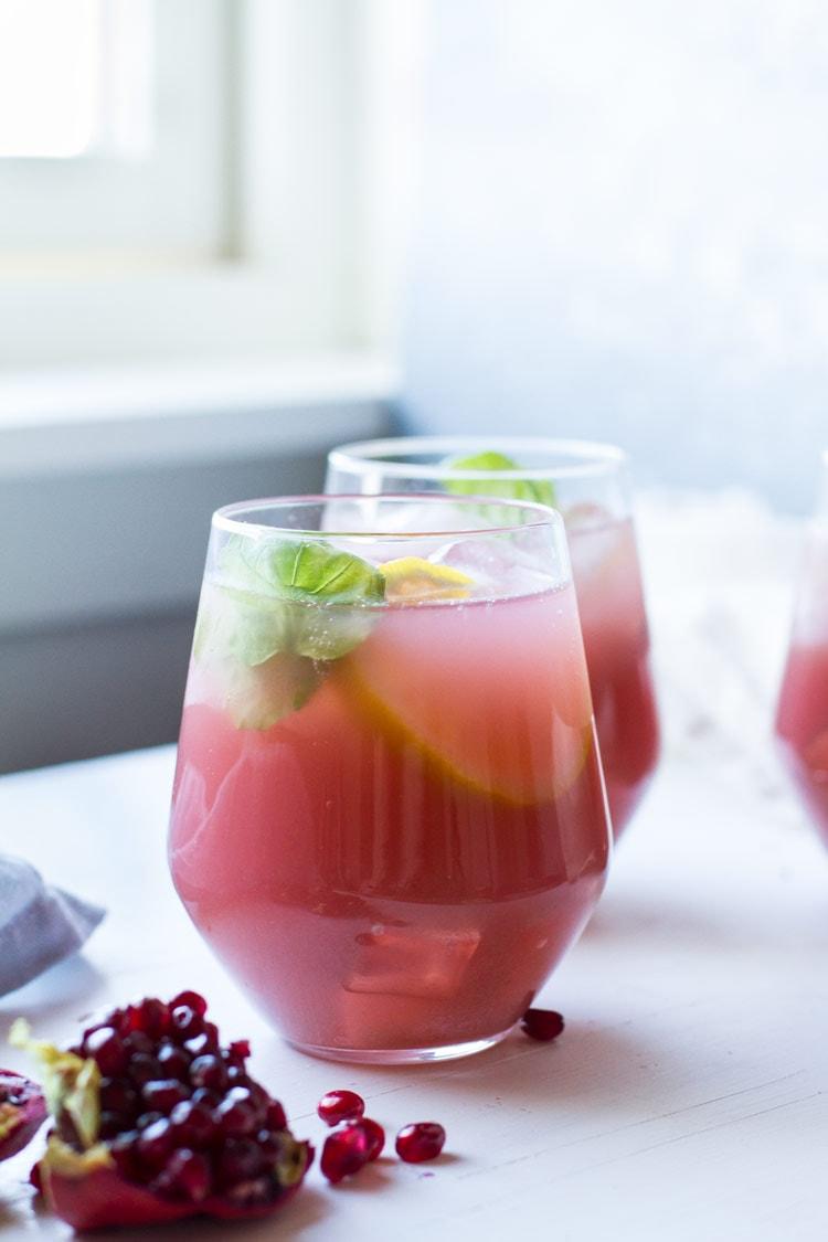 Wine glass, stemless with pink vodka lemonade. Backlighting.
