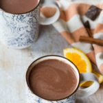 Two blue and white patterned mugs with hot orange chocolate.