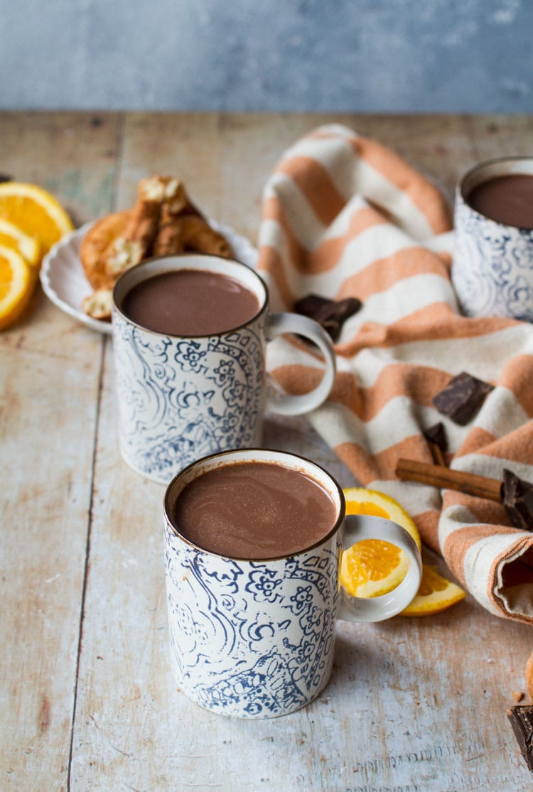 Two blue and white mugs with hot chocolate. Orange slices and an orange colored striped towel in the background.