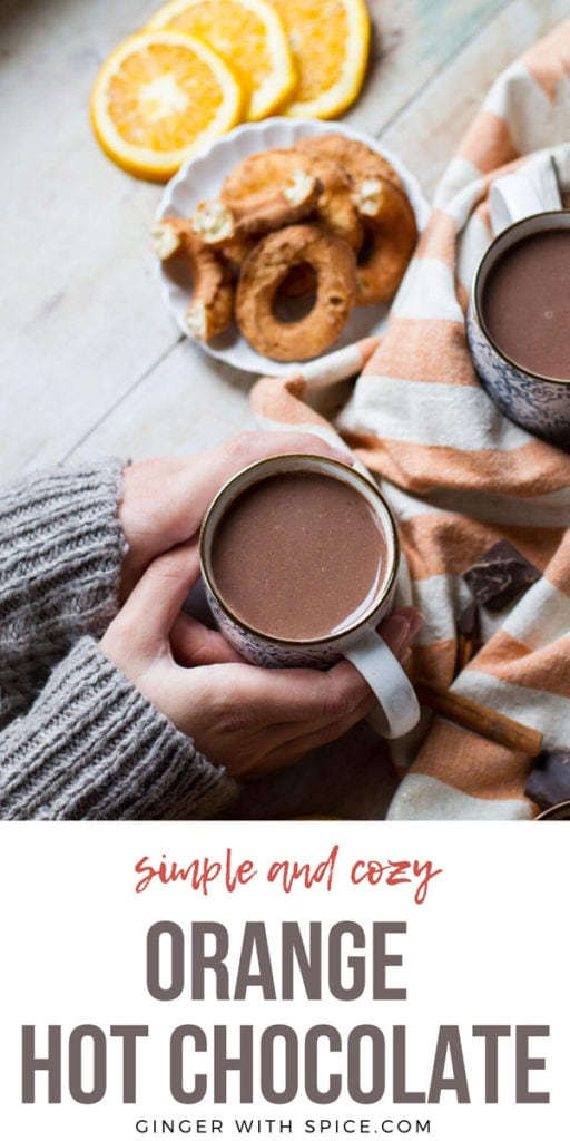 Hands holding a cup of orange hot chocolate. Donuts in the background. Pinterest pin.