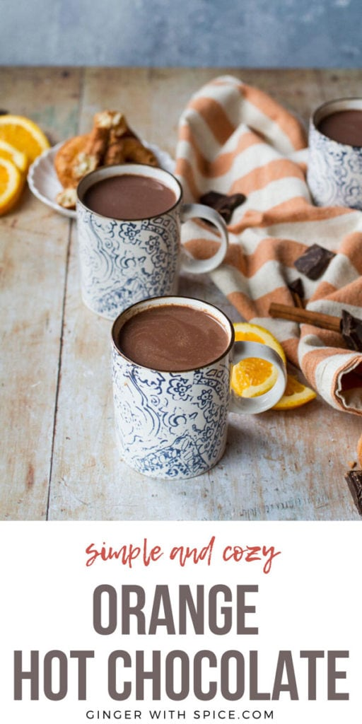 Two blue and white mugs with hot chocolate. Orange slices and an orange colored striped towel in the background. Pinterest pin.