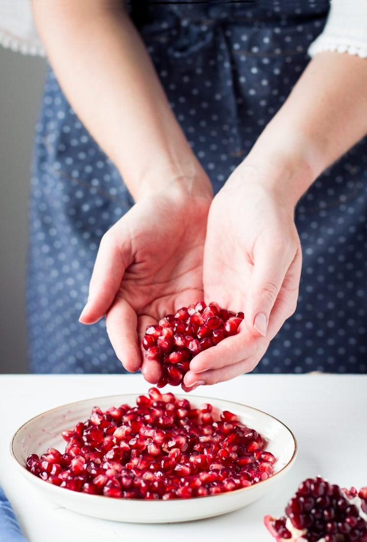 Hands holding pomegranate arils.