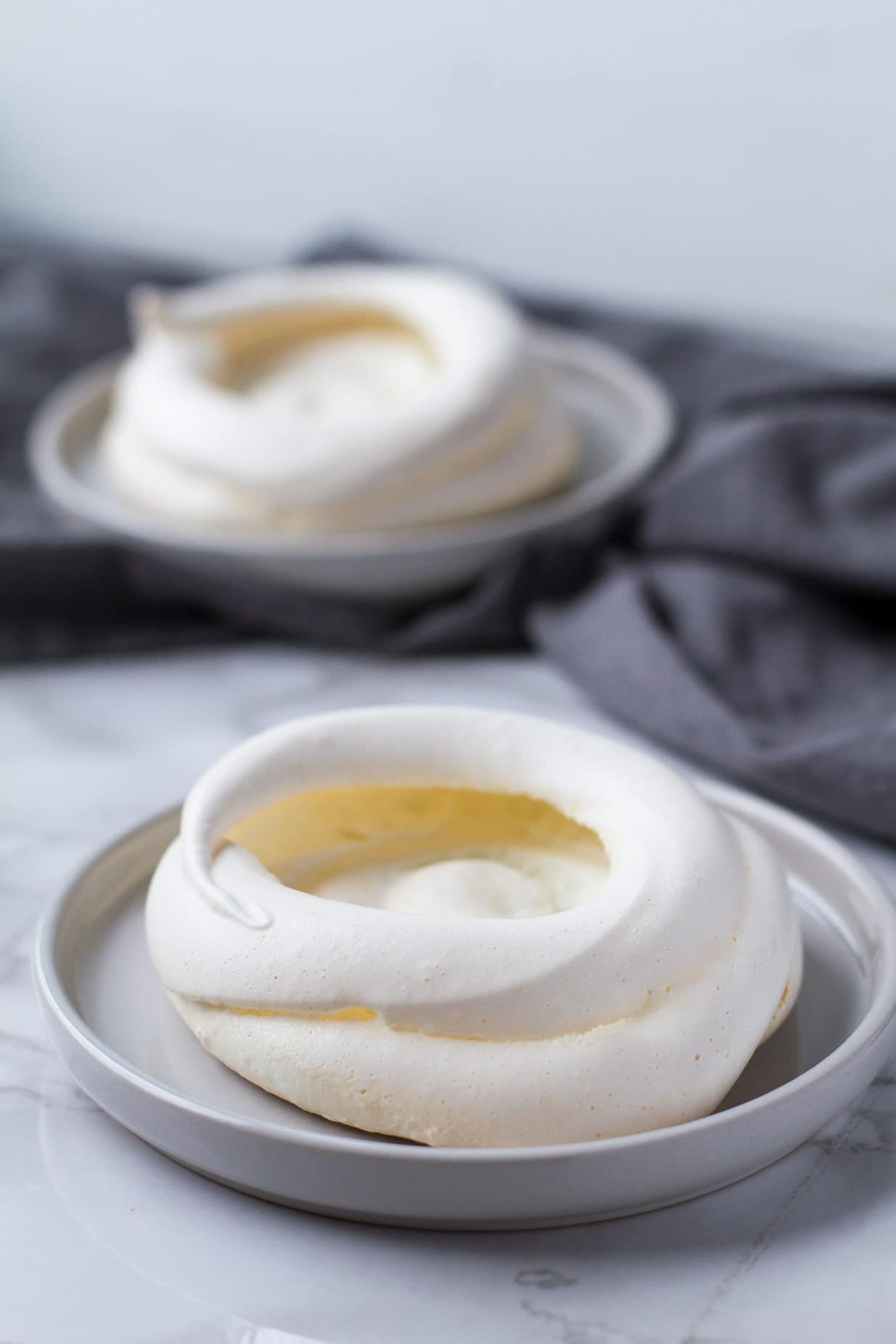 Unfilled pavlova nests on grey plates.
